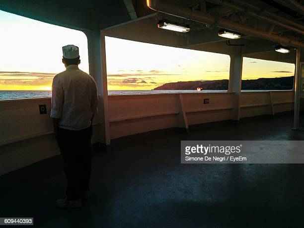 rear view of man looking at sunset view - ponte di una nave foto e immagini stock