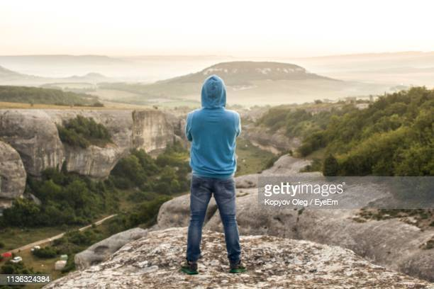 rear view of man looking at view while standing on mountain - hood clothing stock pictures, royalty-free photos & images