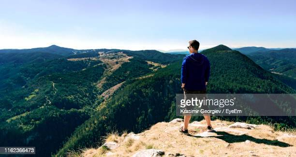 rear view of man looking at view while standing on mountain - krasimir georgiev stock photos and pictures