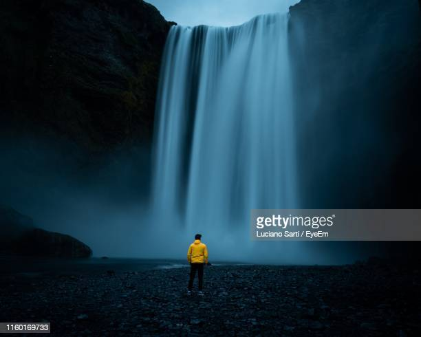 rear view of man looking at waterfall - natural phenomena stock pictures, royalty-free photos & images
