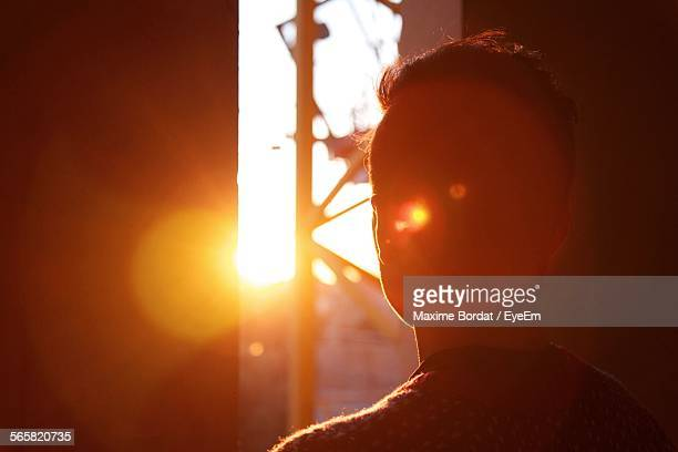rear view of man looking out through azar door at sunset - halo lumineux photos et images de collection
