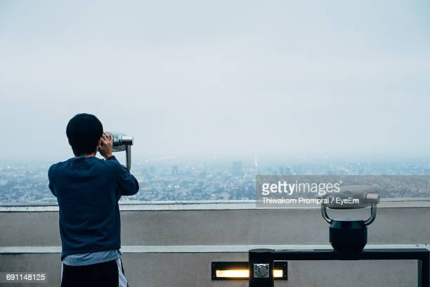 Rear View Of Man Looking Through Binoculars Against Sky During Foggy Weather