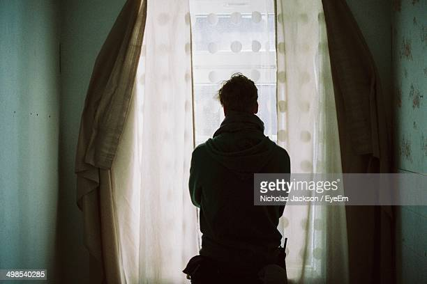 Rear view of man looking through curtained window