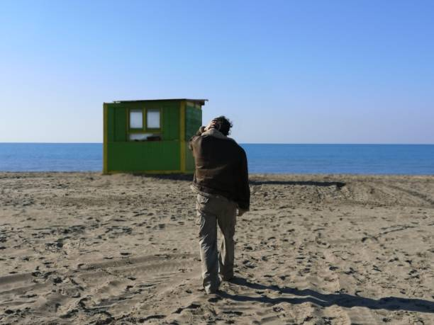 Rear View Of Man On Beach Against Clear Sky