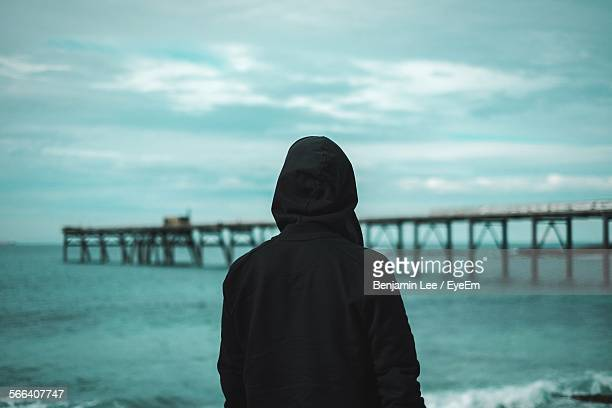 rear view of man on beach against sky at dusk - hood clothing stock photos and pictures