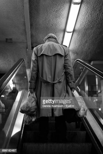 Rear View Of Man On Escalator