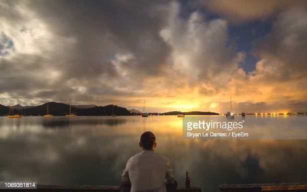 rear view of man on lake against sky during sunset - whangarei heads stock pictures, royalty-free photos & images