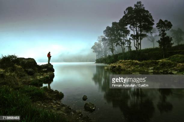 Rear View Of Man On Lake Against Sky