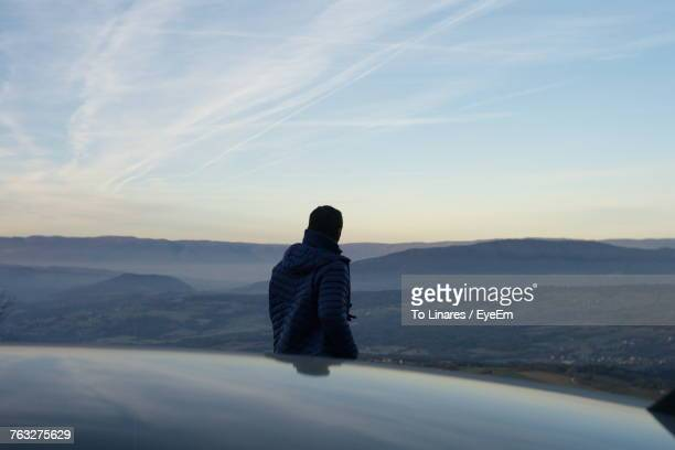 Rear View Of Man On Mountain Against Sky During Sunset