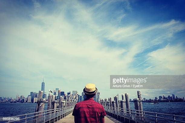 Rear View Of Man On Pier Leading Towards City Against Cloudy Sky