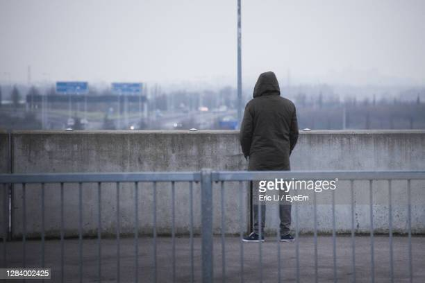 rear view of man on railing by river in city - suicide stock pictures, royalty-free photos & images