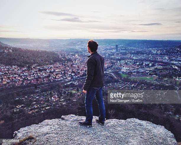 rear view of man on rock against cityscape - thuringia stock pictures, royalty-free photos & images