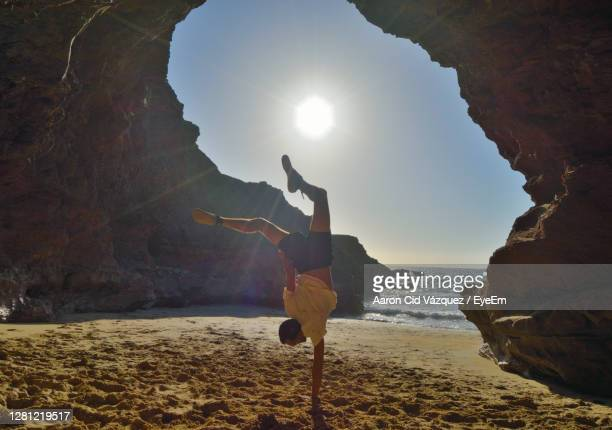 rear view of man on rock at beach against sky - arch stock pictures, royalty-free photos & images