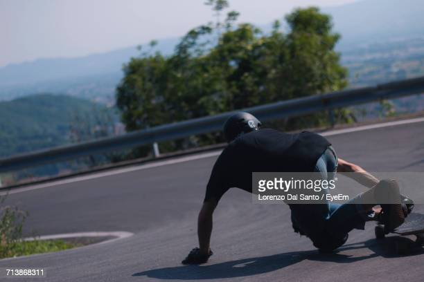 Rear View Of Man On Skateboard On Road