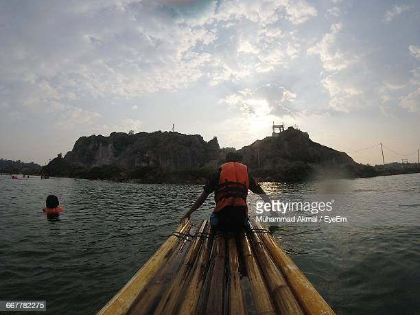 Rear View Of Man On Wooden Raft In Sea By Mountain Against Sky