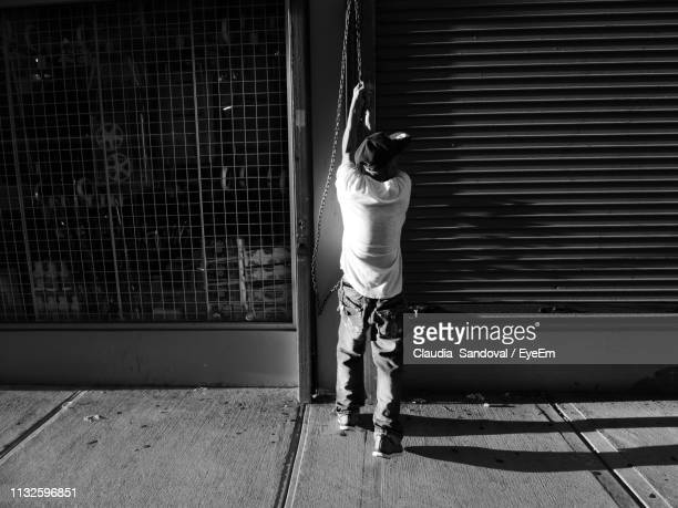 rear view of man opening shutter of store - shutter stock pictures, royalty-free photos & images