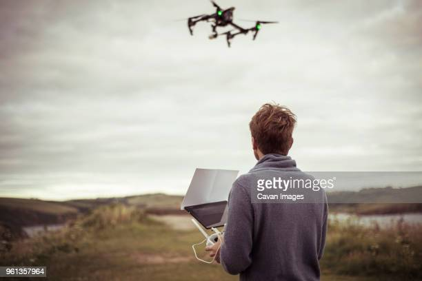 rear view of man operating drone camera while standing on field - drone foto e immagini stock