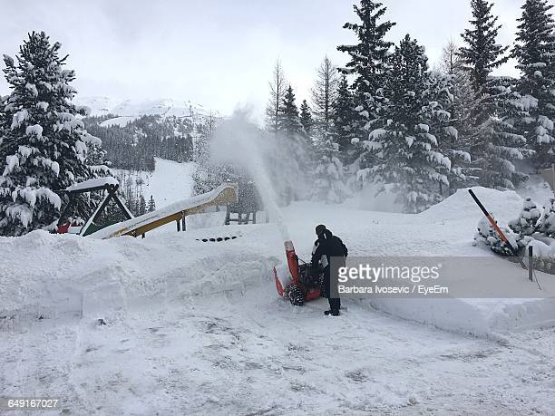 Rear View Of Man Operating Snowblower In Playground