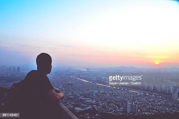 rear view of man overlooking cityscape during sunset - cityscape stock pictures, royalty-free photos & images