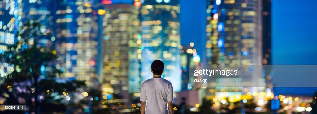 Rear view of man overlooking illuminated city skyline of Hong Kong : Stock Photo
