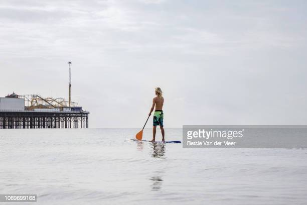 Rear view of man paddleboarding towards pier at sea.
