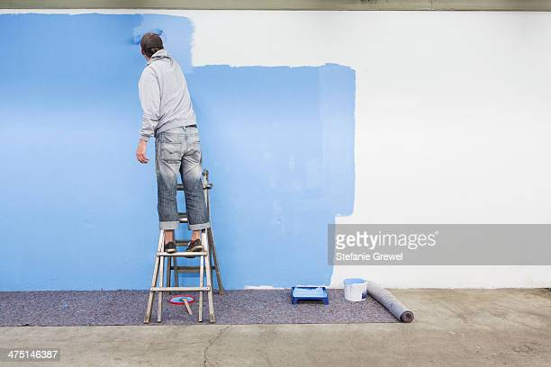 Rear view of man painting wall blue