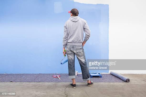 rear view of man painting wall blue - stefanie grewel stock-fotos und bilder