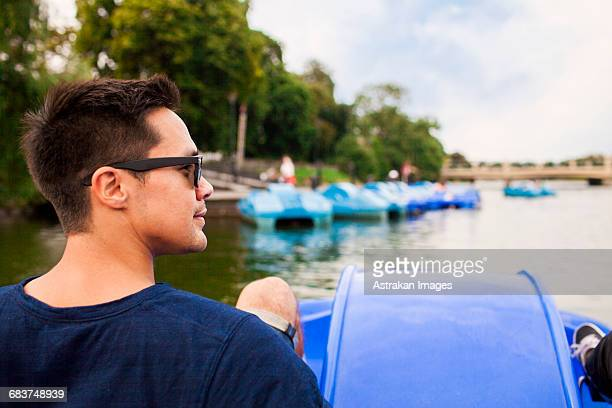 Rear view of man pedal boating on river in city