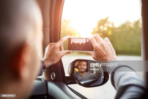 Rear view of man photographing from mobile phone with reflection in side-view mirror