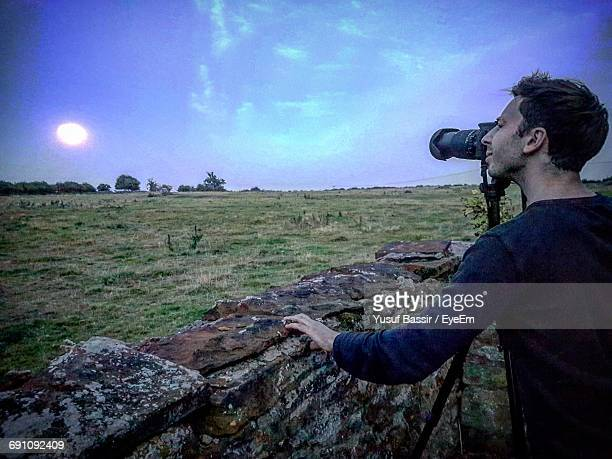 Rear View Of Man Photographing Moon At Dawn