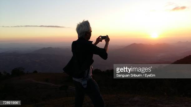 rear view of man photographing mountains from mobile phone during sunset - fotohandy stock-fotos und bilder