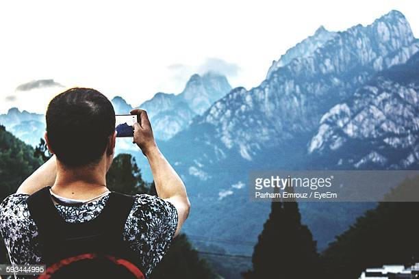 rear view of man photographing mountains - parham emrouz stock pictures, royalty-free photos & images