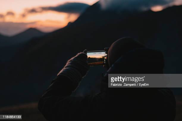 rear view of man photographing silhouette mountains with phone at sunset - fabrizio zampetti foto e immagini stock