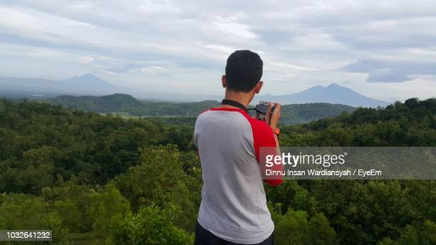 Rear View Of Man Photographing Trees And Mountains Through Camera