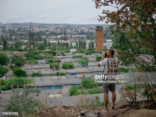 rear view of man photographing while standing against cityscape - moldova stock pictures, royalty-free photos & images