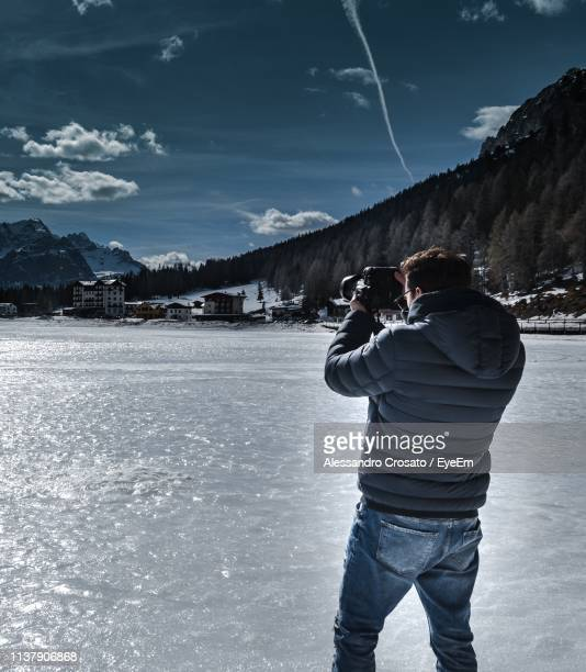 Rear View Of Man Photographing While Standing On Frozen Lake