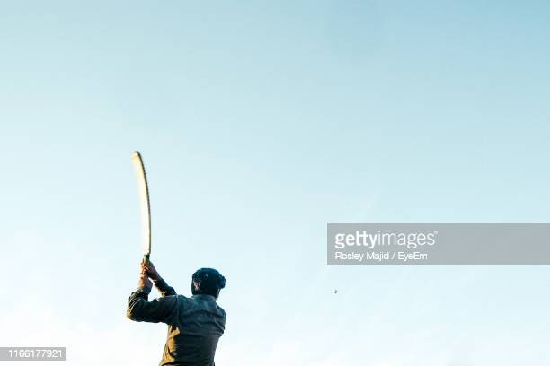 rear view of man playing cricket while standing against clear sky - cricket bat stock pictures, royalty-free photos & images