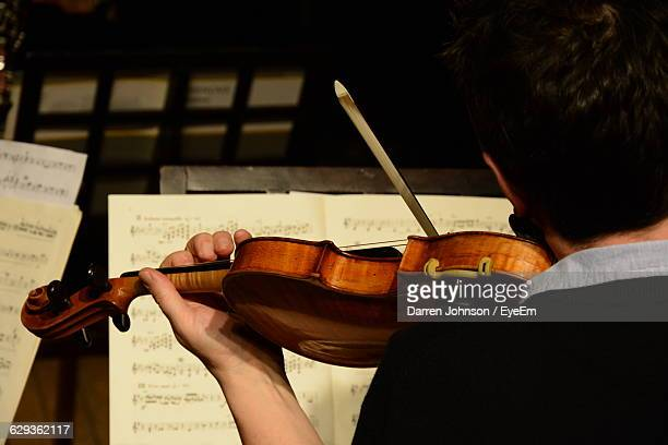 Rear View Of Man Playing Violin