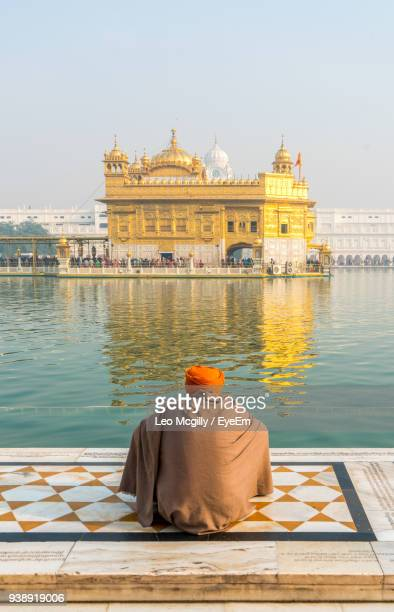 rear view of man praying against golden temple amidst standing water - amritsar stock pictures, royalty-free photos & images
