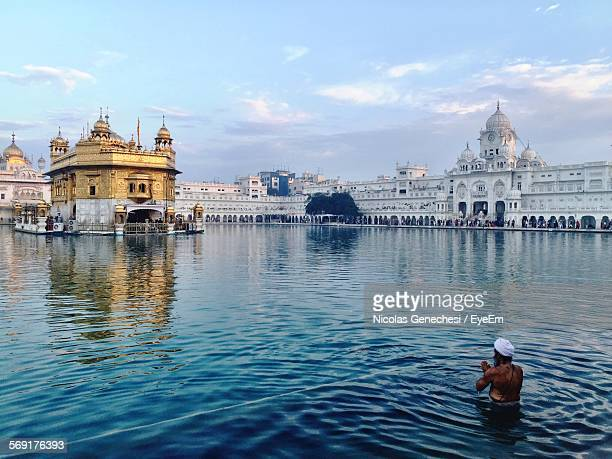 Rear View Of Man Praying In Pond At Golden Temple