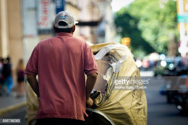 rear view of man pushing loaded cart on street - andres ruffo fotografías e imágenes de stock