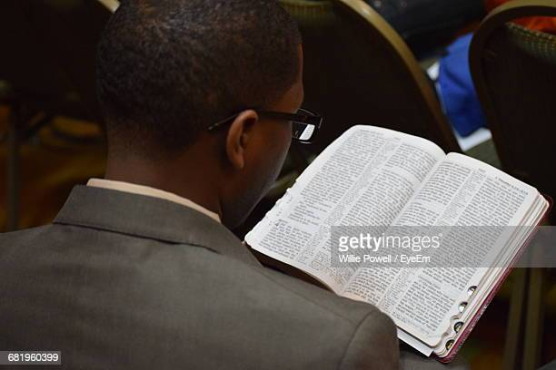 Rear View Of Man Reading Bible In Church