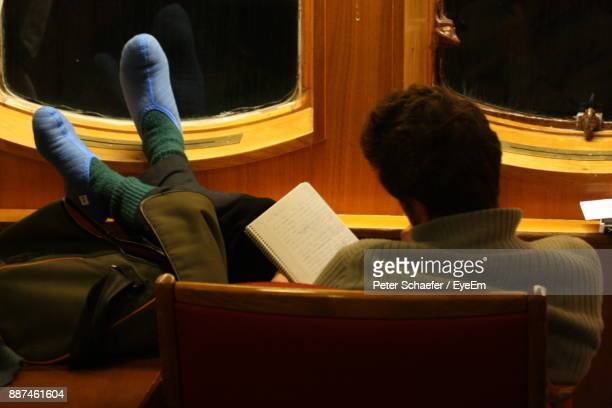 Rear View Of Man Reading Book While Sitting On Chair Indoors