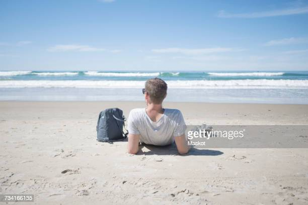 rear view of man relaxing by backpack at beach on sunny day - sdraiato foto e immagini stock