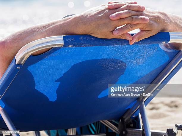 Rear View Of Man Relaxing On Lounge Chair At Beach