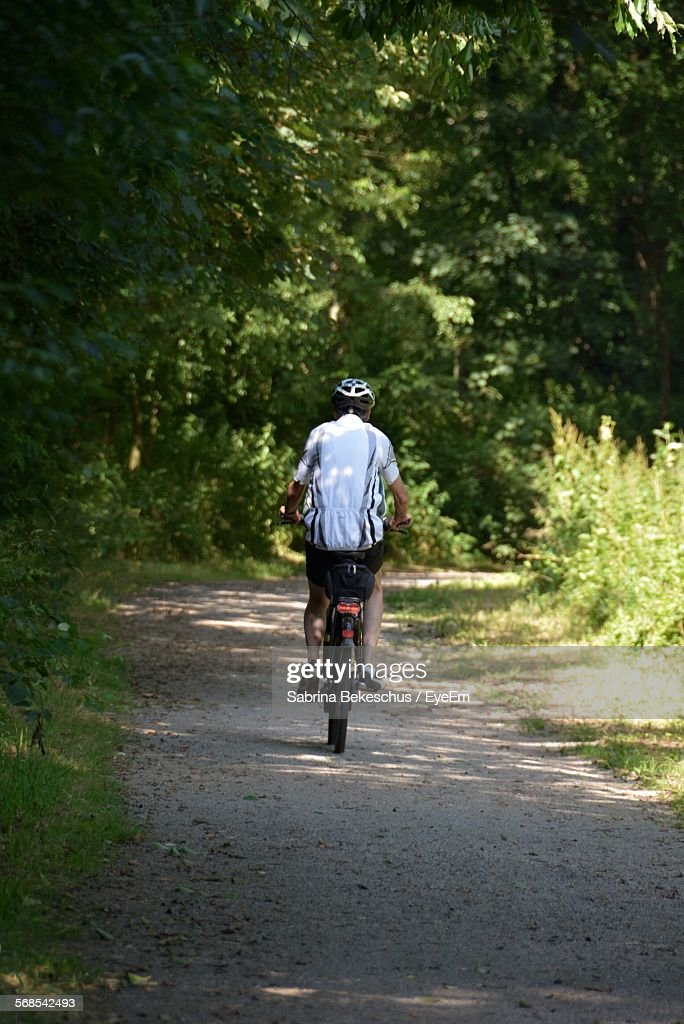 Rear View Of Man Riding Bicycle On Dirt Road In Forest : Stock Photo