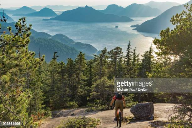 rear view of man riding bicycle on mountain against sky - カナダ バンクーバー ストックフォトと画像