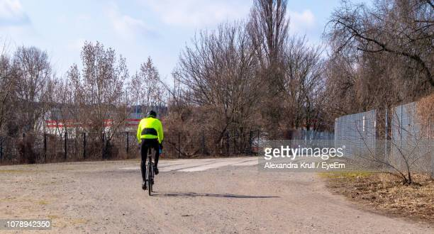 Rear View Of Man Riding Bicycle On Road Against Bare Trees