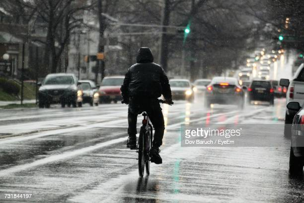 rear view of man riding bicycle on road in winter - barulho stock pictures, royalty-free photos & images