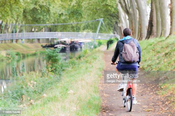 rear view of man riding bicycle on road - canal du midi photos et images de collection